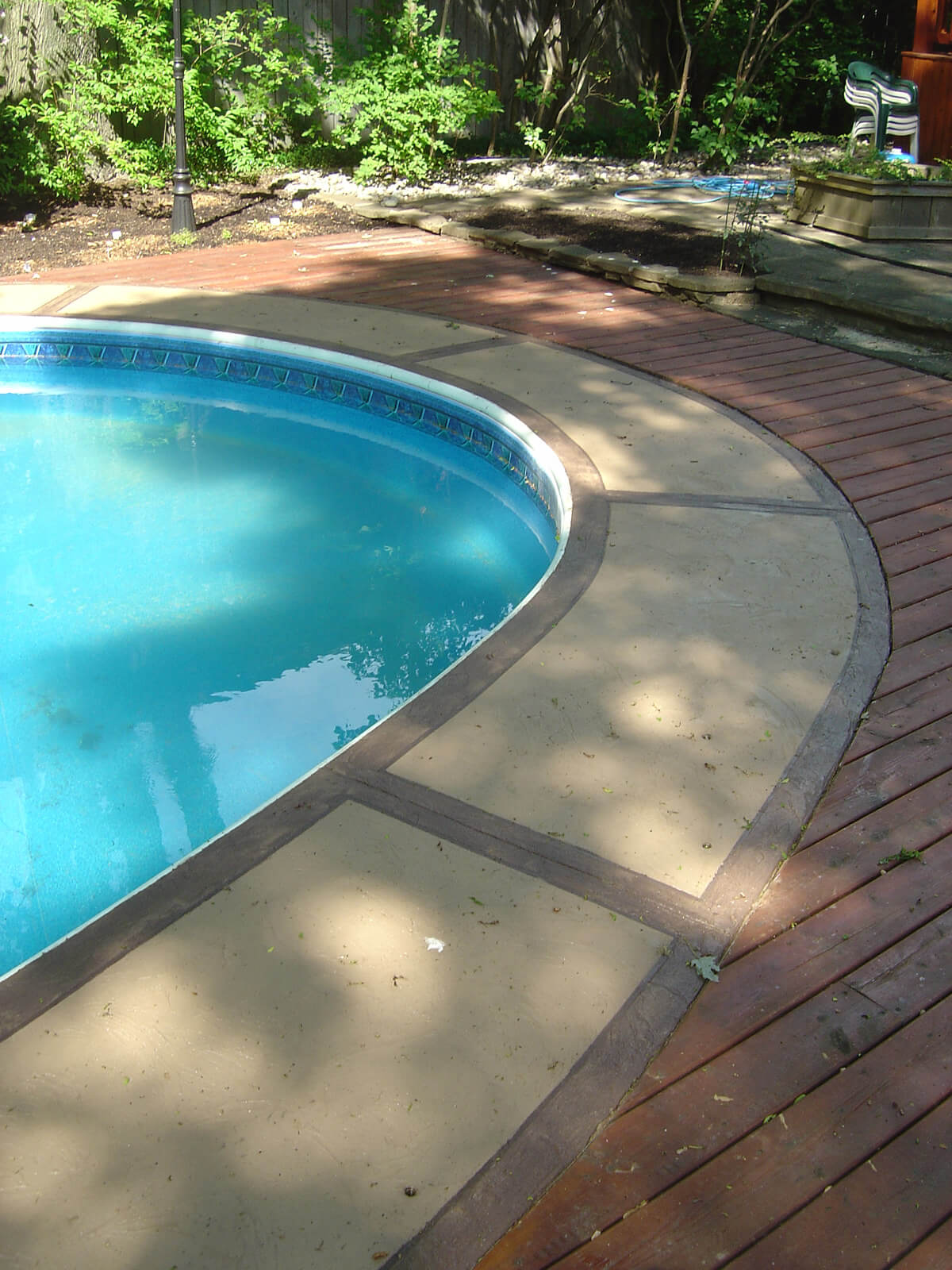 Outdoor swimming pool deck with concrete walkway stone